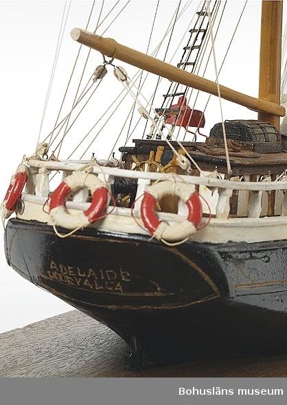 """Föremålet visas i basutställningen Uddevalla genom tiderna, Bohusläns museum, Uddevalla.  Fartygsmodellen föreställer barkskeppet """"Adelaide"""". Båttypen är en tremastad bark, fastsatt mot en platta av mahogny, L 100, B 200 mm.  Skrovet visas från vattenlinjen och uppåt, vattenlinjemodell, och är svartmålat med en guldfärgad linje under bredgången som i för och akter avslutas med en dekorativ slinga. Strax bakom mesanmastens röstjärn står med versaler i guld på båda båtsidor """"ADELAIDE"""" samt på akterspegeln på samma sätt """"ADELAIDE"""" och därunder """"UDDEVALLA"""".  Modellen är fullt riggad men saknar segel. I stormastens topp sitter den blågula rederiflaggen med ett """"S"""" för Sannes Rederiaktiebolag, Johan Newton Sannes rederirörelse.  På övre mesangaffeln sitter nationsflaggan med unionsmärket, """"sillsalaten"""". Flaggorna är tillverkade av ripsvävt band, troligen siden, med moaréeffekt. Två stockankare hänger under kranbalkar med kättingar i kabelgatt till två ankarspel där kättingarna går ned i däck framför förpiksluckan i ett kabellarium till ett grönmålat rattspel som står på ömse sidor om stormasten. Framför kajuthuset står gångspelet capstan) som också är grönmålad. Modellen har ratt med rattaxel, styrpinne och styrkätting i block. Framför ratten står ett nakterhus. Modellen har kajuthus med skylight. Mesanmasten går ner i kajuthustaket. Framför detta ligger två vitmålade livbåtar upp-och-ner på en ställning ovanför bakre lastluckan. Framför stormasten är främre lastluckan placerad. Framför denna ligger tre vitmålade färskvattentunnor. Bakom fockmasten är skansen med ett skylight och kabyss.  På skanstaket ligger den tredje livbåten surrad samt står tre pytsar. Framför ankarspelet sitter skeppsklockan i en ställning. Framför denna sitter klyvar- och jagarbommen i bogsprötet som har stampdävert och stampstag. Framför mesanvanten, på relingens vitmålade balustrad är babords rödmålade respektive styrbords grönmålade lanterna. På akterns relingsbalustrad   hänger tre frälsarkrans"""