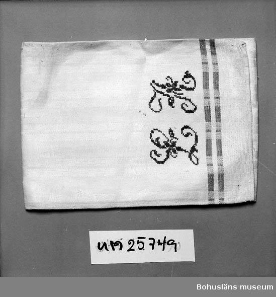 """Längs kanterna två röda partier. Stort broderat monogram i korsstygn """"LA"""" Laura (Lovisa) Andreasson f 1854 gift med Martin Andreasson, f 1854 d 1925 fiskare och kyrkvärd i Gravarne samt innehade båten """"Frifararen"""" numera ägd av Fornminnessällskapet Vikarvet och uppsatt vid dess museum i Lysekil. Givarens mors föräldrar.  Personuppgifter se UM025730 och UM025739."""