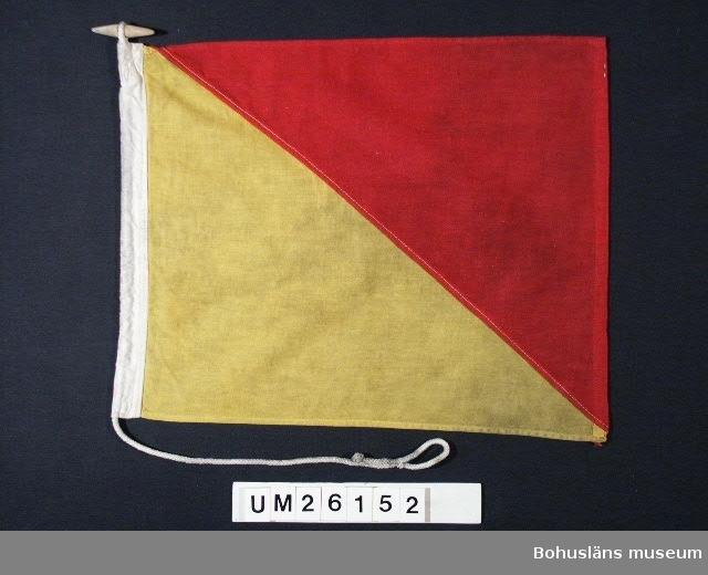 """Föremålet visas i basutställningen Kustland, Bohusläns museum, Uddevalla.  Diagonalt delad i två fält, ett rött och ett gult.  Betyder: """"Man överbord"""".  Använd för fartygssignalering på  Ångfartygs AB Bohuslänska Kustens båtar. Användning se UM026139  Personuppgifter se UM026024"""