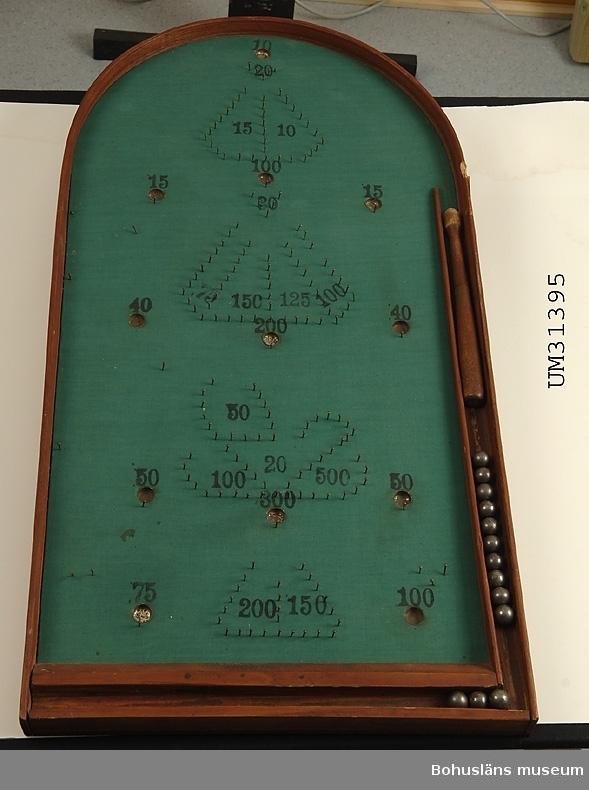 Fortunaspel med stålkulor och pinne av trä. Svagt lutande halvoval spelplan med rödbetsade kanter. Undertill en tvärställd slå som gör att spelplanen lutar mot spelaren.Spelplanen  täck av grönt bomullstyg. Spikar i olika mönster runt numrerade koppar av olika valörer/svårighetsgrad, från 10 till 500 poäng. Fack med 13 tillhörande spekulor av stål, kö av svarvat trä som ligger i långsidans bana där kulorna skall skjutas ut.  Andra tänkbara namn på spelet är Bagatelle, Baffle ball och Pinboard game.  Ur Nationalencyklopedien, Internet 2009: Fortunaspel, ett spel i vilket man sätter stålkulor i rörelse på ett lutande bräde; kulorna ger poäng alltefter var de hamnar. Spelet uppfanns i USA 1871 som en utveckling av bagatelle och fick namnet fortuna när det kom till Sverige på 1890-talet.  Föremålet har använts av familjen Abrahamson i deras sommarstuga i Sundsandvik, byggd 1939. För ytterligare upplysningar om förvärvet, se UM031385.