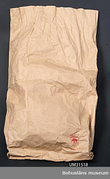 Förpackning för hönsfoder av snäckskal. Papperssäck av brunt kraftpapper i fyra lager, rymmande 50 liter, med tryckta texten: DIAMANTSKAL BRÖDERNA STEENE A-B UDDEVALLA inom cirkel med illustration av diamant. Härunder i röd text: TVÄTTAD  VARA  På baksidan tryckt med röd text: JOHNSONS EMBALLAGEINDUSTRIER  OTTERBÄCKEN SWEDEN