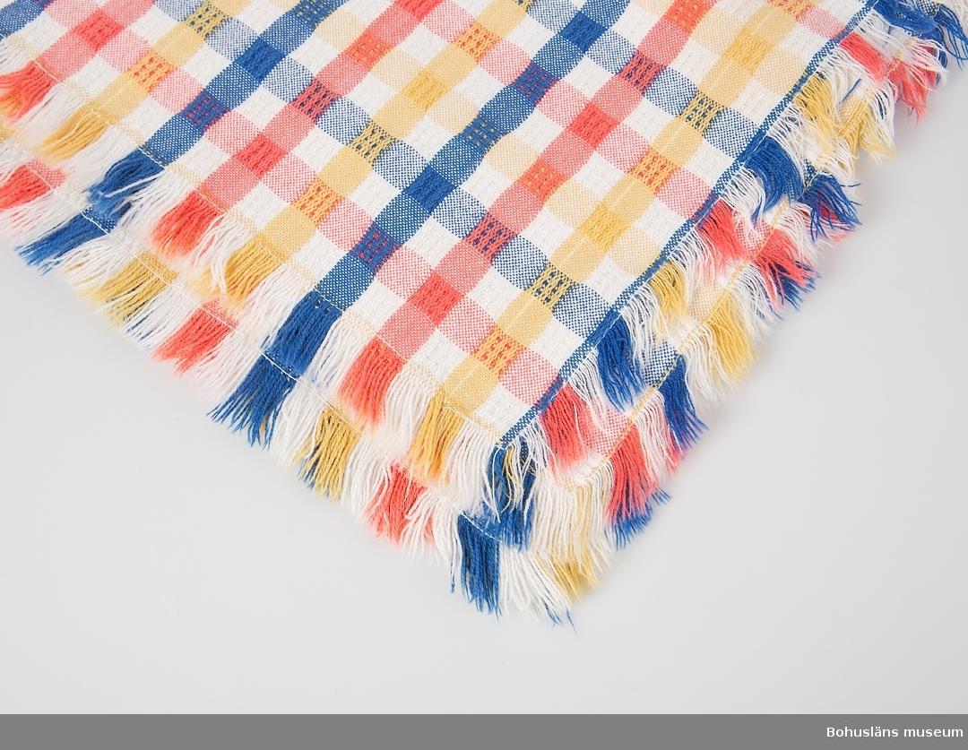 Kvadratisk rutig duk av bomull med kort frans på alla sidor. Vävd i drällmönster, så kallat hålkrus; varp och inslag i vitt, rött, blått och gult.
