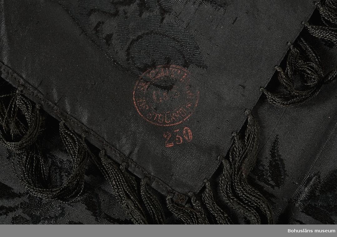 Svart sidenschal med frans. Jaquardvävt heltäckande blommönster. Handknuten frans, 11 cm lång. Maskinfållad. Rund röd stämpel i ena hörnet med texten C&S STOCKHOLM.  Plagget har tilllhört Hilma Lovisa Karlsdotter (1878 - 1965), dotter till hemmansägaren och styrmannen Karl Berndtsson (1846 - 1933) och Anna Maria Berndtsdotter (1848 - 1938) på Hallsbäck Uppegård.  I gåvan ingår ytterligare schalar av siden och bomull liksom ett handvävt lakan, se UM031735 - UM031739.