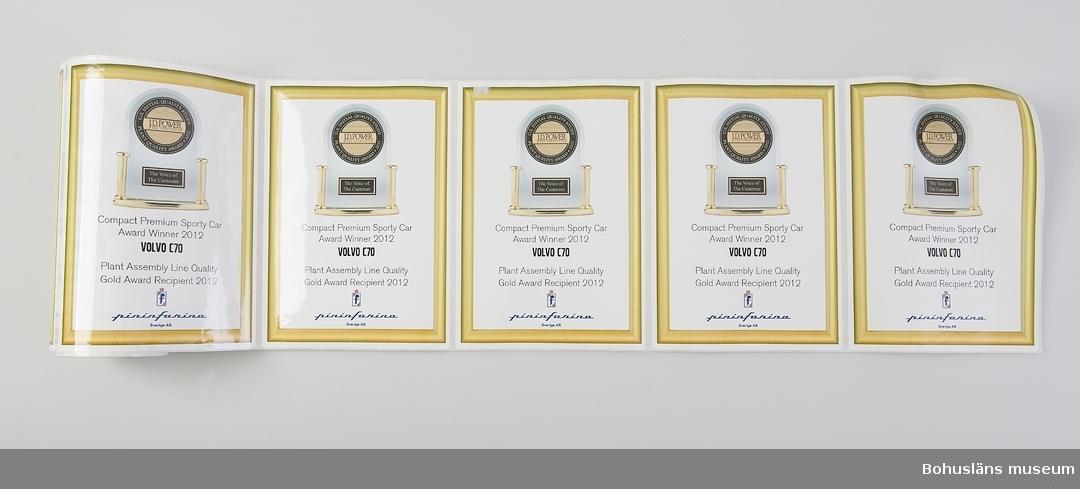 Föremål från bilfabriken Pininfarina / Volvo i Uddevalla. Dekaler på rulle. Med dekaler och guldhattar firades  att Pininfarina i juli 2012  fick en fin internationell kvalitetsutmärkelse.
