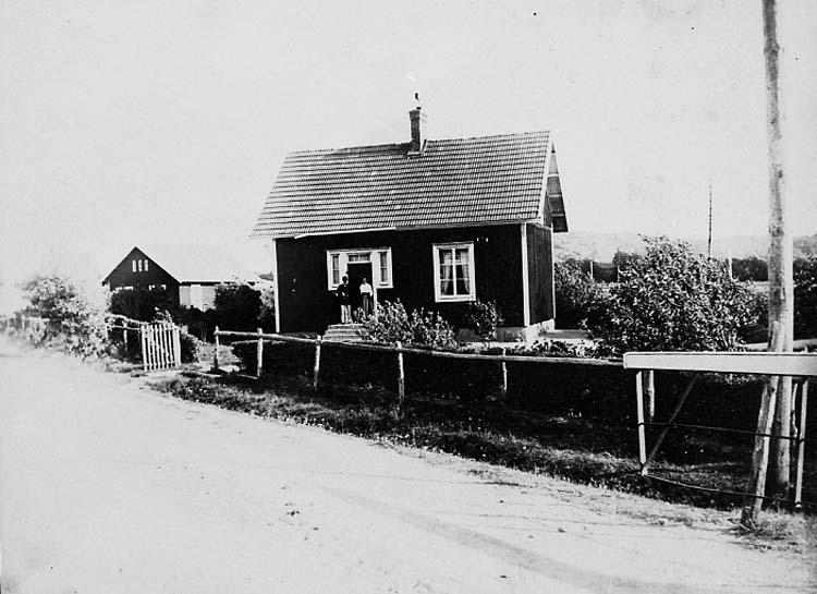 """Enligt fotografens notering: """"Kåkenäs banvaktstuga nr 460. På trappan står Edvin och Adelina Andreasson någon gång i början av 1920-talet. Fram till 1960-talet hade SJ banvakter som bodde vid banan och ansvarade för en mindre sträcka. De inspekterade varje dag, vardag som söndag, och skötte underhållet utom större reparationer""""."""