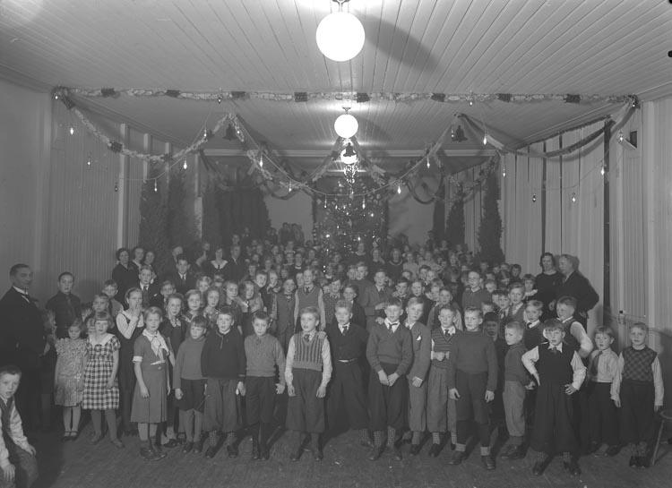 """Text som medföljde bilden: """"1936. 50. Julgransfest Föreläsningsalen Munkedal"""".  Uppgifter från Munkedals HBF: """"Dessa årligen återkommande julfester arrangerades av Munkedals AB, som stod för underhållning och förtäring""""."""
