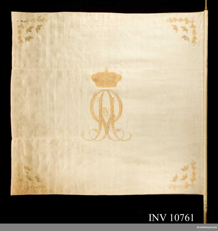 Grupp B.  Duk: Tillverkad av vit sidenkypert med målade emblem, i mitten Gustav  Adolfs krönta namnchiffer i guld och rött, i hörnen korslagda   lagerkvistar och därimellan tre öppna kronor, allt i guld rött. Fäst vid stången med sidenband och förgyllda spikar.  Stång: Av vitmålad furu. Holk finns så även spets med lilla riksvapnet.