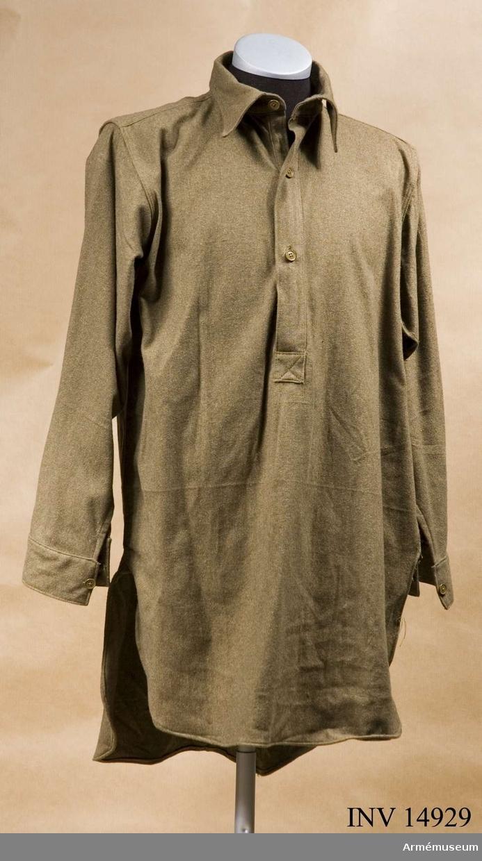 """Grupp C I. Skjorta m slips. Blusjacka i skjortform av khakityg. Knäppes vid bröstet m tre khakifärgade benknappar. Krage liggande. Ärmuppslag rakskurna m inskärning och en knapp. På blusens insida, vid kragen, fastsydd tygbit m stämpel """"R. Elwood & Co Size 4, 1946"""" PUBL  AMV Meddelande IX, sida 38.Enl kapten W Granberg."""