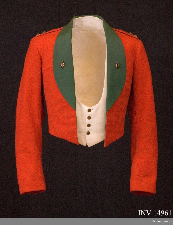 """Grupp C I. Del av mässuniform för överstelöjtnant vid The Worcesterhire Regiment i England: """"scarlet shell jacket"""" med två regementsmärken. Enligt """"Dress regulations 1900"""" av W. Y. Carman fastställdes denna jacka 1896-07-17.  Förmodad gåva från Lt Col PH. Graves-Morris D.S.O. M.C.  Engelsk militärattaché i Sthlm. Buren av givaren."""