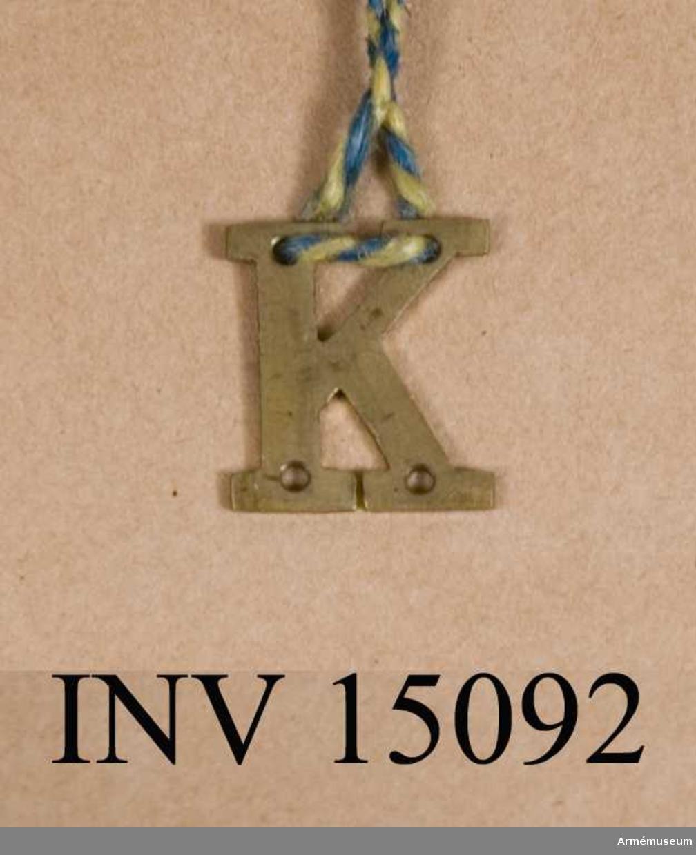 Grupp C I Bokstaven K m/1915 till lägermössa och hatt. För manskap vid infanteriets kulsprutekompanier. Fastställd genom go nr 1591 den 12 november 1915.