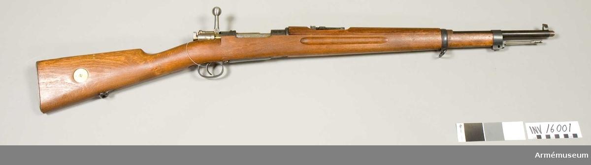 """Gevär m/1938 B. System Mauser. Märkbricka av mässing på kolvens högra sida. Märkt """"O:G."""" Mekanismens handtag är rakt. Vapnet är ett förkortat gevär m/1896, tillverkat år 1898. Mynningsgänga för lösskjutningsanordning. Gängskydd saknas. Riktmedel: ramsikte graderat för avstånd 100-600 m."""