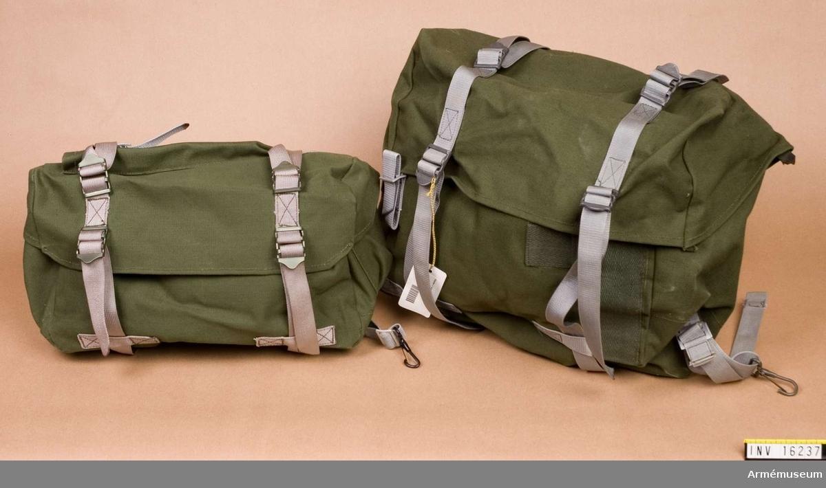 Väska till stridssele. Av grön smärting med grå textilremmar. Har inbyggd metallställning.