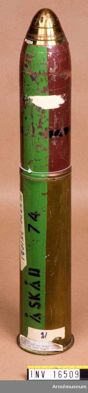 """Patron m/1900.Med granatkartesch m/1900 och spetstidanslagsrör m/1908 (stidar). Patronhylsans l: 278 mm. Märkt: XF 4900 (K 37 69) Skultuna bruk och en krona (Åskåd 74 grön rand. Karteschen märkt """"J"""". Färgmärkning: B svart rand på brun botten. Röret märkt """"M29 4""""."""