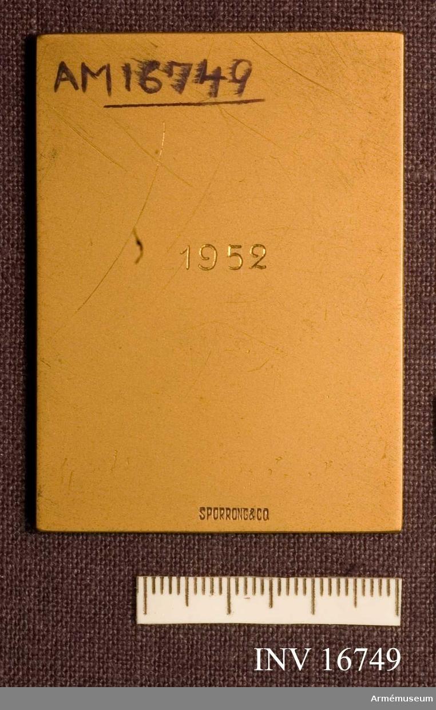 Åtsidan visar på sin övre del en bladcirkel inneslutande en stående och en knästånde skytt, fana och kanon. Under detta står det: Stockholms stads Friv. Skarpskytteförening. Därunder på platta står: T. Jansson. Frånsidan är slät med endast årtalet 1952 inristat och nedtill Sporrong & Co.  1860-1950.