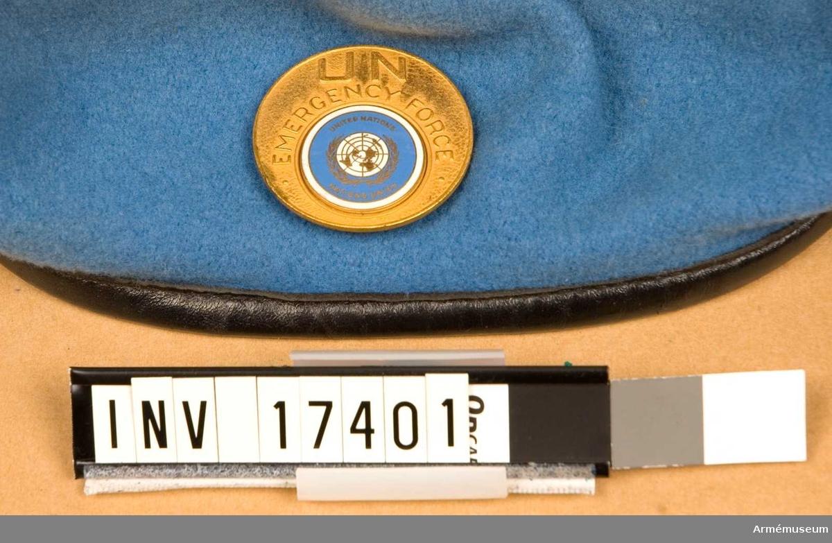 """Grupp C I.  Märke till basker, FN. 1956. För trupp ur Förenta Nationernas övervakningskommission vid Suez och Gaza-remsan i Egypten 1956-67.  På vänstra sidan ett emblem av emaljerad gulmetall med text: """"UN EMERGENCY FORGE United Nations Nations Unies"""".  Foder av svart bomullstyg med märkning: """"Fleur de Lis BERET 6 7/8  Dorothea Knitting Mills LIMITED TORONTO"""". /Beskrivning 1973 S W-ge."""