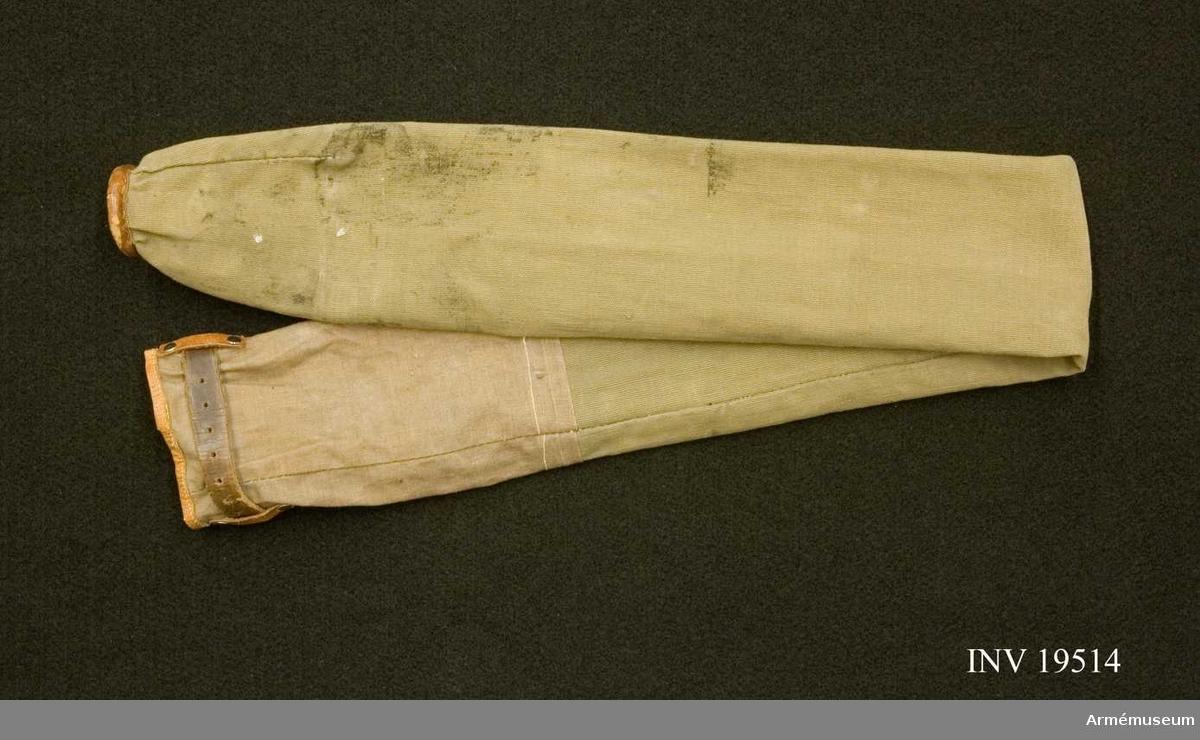 Fodral till kommandotecken  Fodralet är tillverkat i grå smärting. Upptill är det försett med en lädertopp och nedtill ett 3 cm brett lädererband med öglor för knytning med läderband.  Samhörande nr AM 19513-15, standar, fodral, spets.