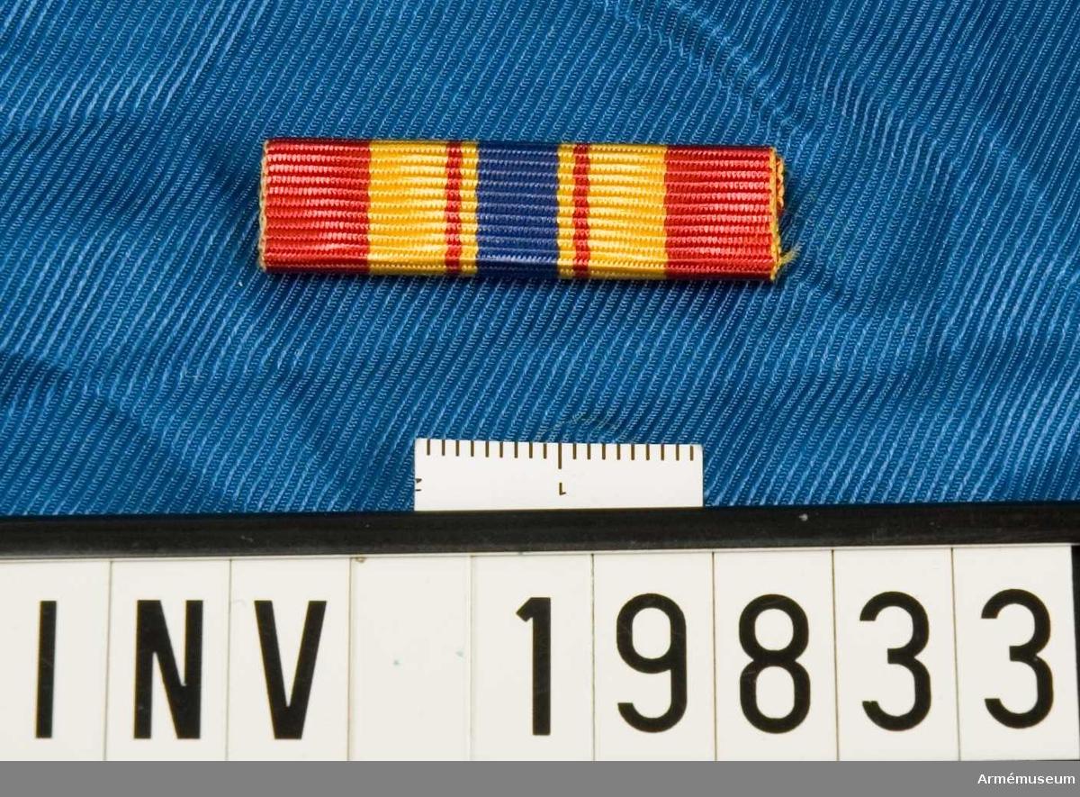 Gult band med breda röda kanter, ett blått band i mitten med ett rött streck på vardera sidan. Släpspännet förvaras i en ask tillsammans med en medalj och en miniatyrmedalj.