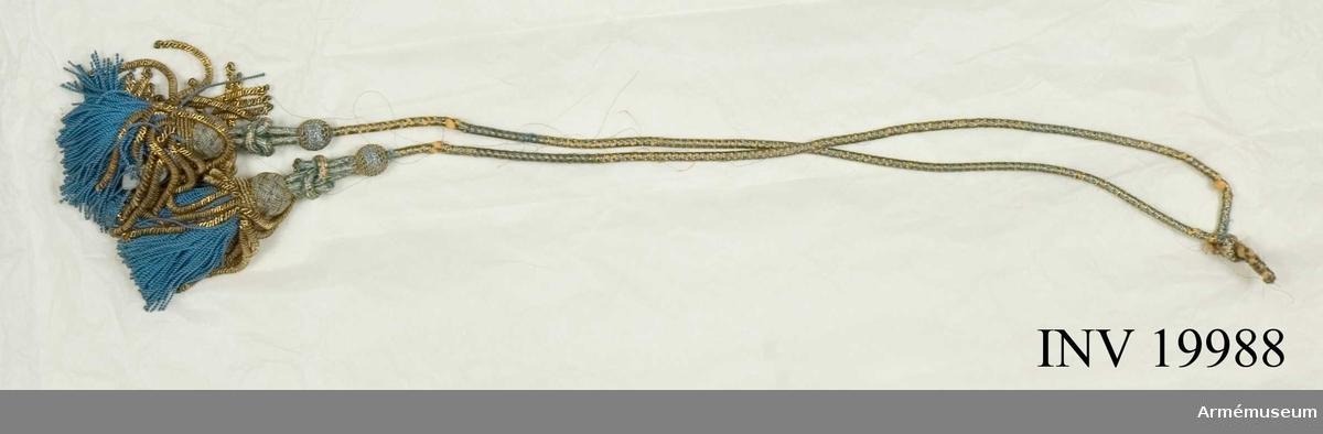 Snoddens blå silke delvis bortnött och den gula kärnan är synlig. Några lösa metalltrådar. Ett par lösa metalltrådar också i den ena tofsen.