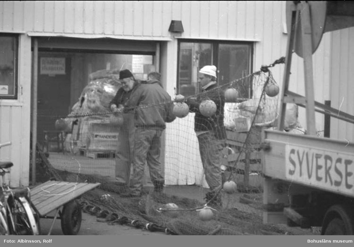 """Enligt fotografens noteringar: """"Syversens trålverkstad. Längst bort Tage Hartvigsson, med ryggen mot oss, Sölve Jakobsson, närmast Ola Berndtzen."""" Fototid: 1996 den 12 januari."""
