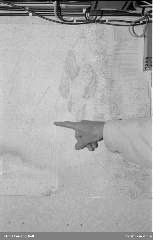 """Enligt fotografens noteringar: """"Ärans sjökort kan se var man trålar. Erling Larsson pekar. Taget med blixt.""""  Fototid: 1996-04-23."""