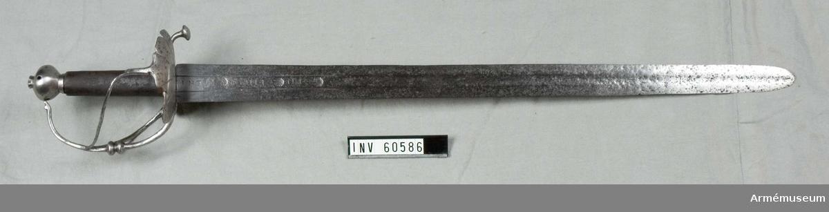 """Grupp D II.  Värja för infanteriet, Tyskland. 1600-talets mitt.  Klingans bredd upptill är 38 mm. Klingan är tveeggad med flata åsar. På var sida finns inskriften INTI DOMINI, varjämte en stämpel med ett krönt T är inslaget tre gånger på var sida. Klingan är förkortad.  Fästet är av järn och av samma typ som de s k """"Schwedensäbel"""". Knappen har formen av ett uppifrån hoptryckt klot, har låg nitknapp och mycket kort hals. Kaveln är klädd med läder. Parerstångens bakre arm är nedböjd och slutar i en knapp. Framtill övergår parerstången i båge i  handbygeln, som på mitten pryds med ett par knappar och vars  övre ände är instucken i ett hål i knappen. På yttersidan finns en ganska stor parerplåt, vars kant pryds av fem avrundade uddar och vars undre sida har sex strålformigt utgående räfflor. Från parerplåtens yttre kant går en S-formigt krökt spång till något ovanför handbygelns mitt, varjämte en nu förkommen bygel från samma ställe på parerplåten går till knappen. På innersidan finns en liknande men mindre parerplåt, vars kant pryds av avrundade uddar och vars undersida har fyra strålformigt utgående räfflor. Från denna parerplåts kant går en tumbygel till kavelns nedre del och från parerplåten något framför tumbygeln går en svagt S-formig spång till handbygeln, som den träffar mitt emot ytterspången. Alla spänger, stänger och byglar har cirkelrunt tvärsnitt och är fästa vid varandra genom lödning med koppar."""