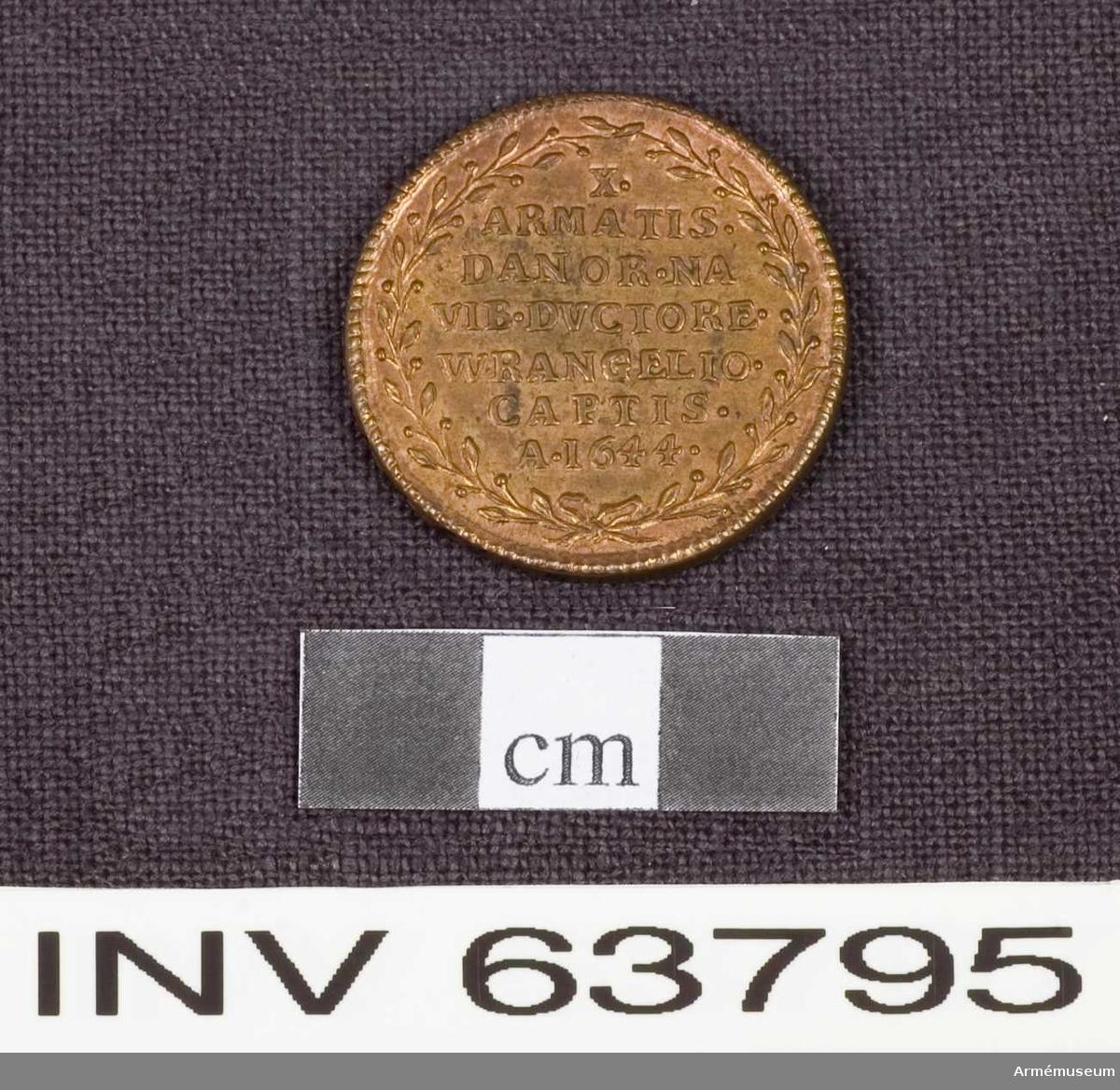 """Grupp M. Medalj av 6. storleken. Slaget vid Fernum den 13 oktober 1644 under Carl Gustaf Wrangels befäl. Medaljen är av brons och pärlkantad på båda sidor.   ÅTSIDAN: """"CHRISTINA. REGINA"""". Bröstbild åt höger i mantelveck.  FRÅNSIDAN: """"X. ARMATIS. DANOR. NAVIB. DYCTORE. WRANGELIO. CAPTIS. A.1644"""" på sju rader inom en lagerkrans."""