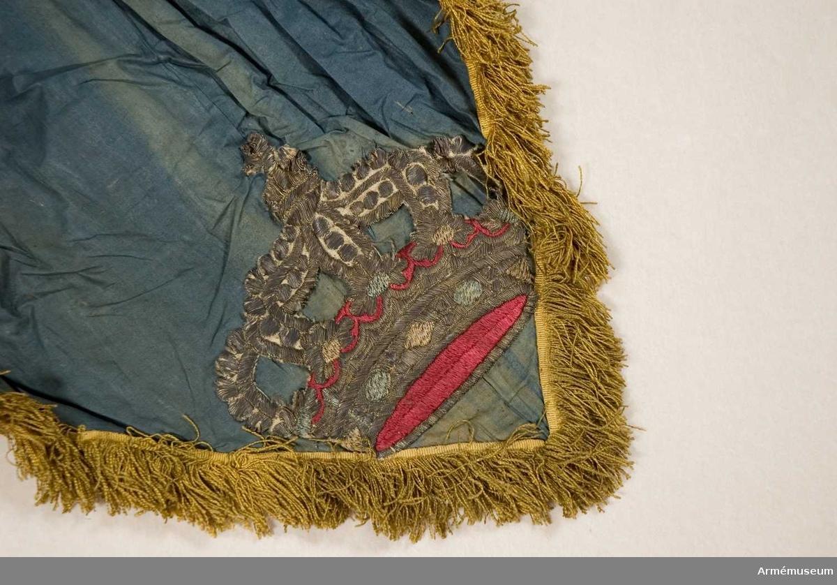Standar.  Duk av enkel blå bomullslärft.  Fäst i ena dukhörnet, hopveckad upptill (ev. tillfälligt hopkommen). I det på stången nedhängande hörnet applicerat en sluten broderad krona i guld och silver med kronfoder i rött (antagligen tagen från en annan fana).  Frans, enkel av gult silke.  Stång av trä, grönaktigt målad. Större delen kannelerad. Saknar holk. Löpande bärring. Grepp klätt med tyg och frans.  Katalogisering:Gudrun Ekstrand/Rebecka Enhörning, inmatning-utskrift PAr 1996-12-18.  Deposition till Armémuseum januari 1997.  Leif Törnqvists kommentar vid inventering 2007: Detta är inget standar utan en festdekoration av någon sort.