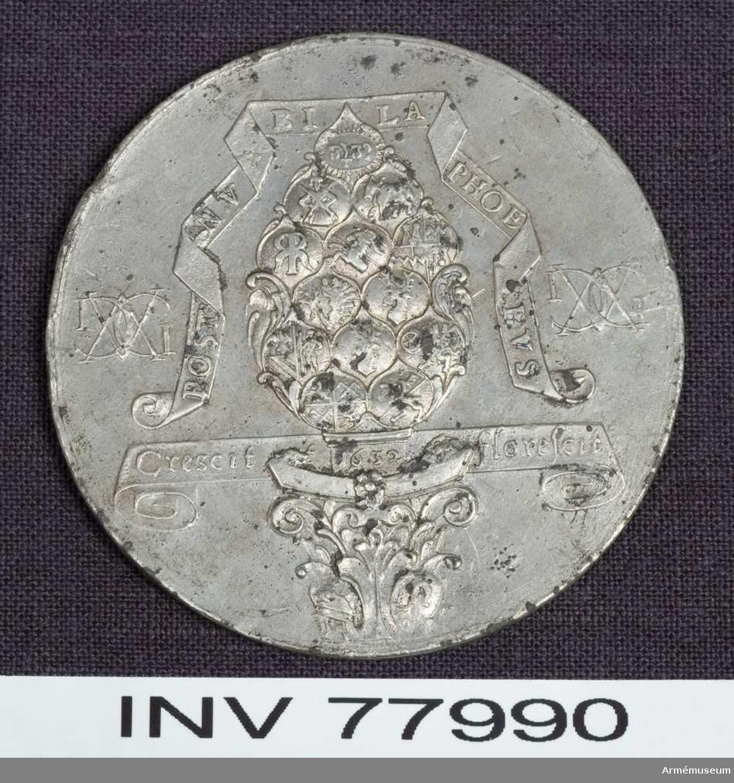 """Grupp: M.  Medalj. Gustav II Adolf. Augsburg öppnar sina portar för Gustaf II Adolf 1632 den 14 april. Kantskavet på flera ställen skadat i randen.  Åtsidan: POST NV BI LA PHOE BVS. på ett veckat band omkring """"der Augsburger Pyr"""" (kotten staden Augsburgs vapenbild), vars fjäll består av 13 små sköldar, av vilka 12 innehålla magistratpersonens vapen, den 13de och översta ett strålande JHVH (med hebreiska bokstäver). Kottens skaft, varpå läses: 1632, står på ett pelarkapitäl, prytt med två vapensköldar. På ett band bakom pelarens skaft: Crescit et florescit. På ömse sidor ett dubbelt monogram av bokstäverna GA, vilk avse dels konungens namn, dels stadens antagna benämning """"Augusta Gustava"""" (i st. f den äldre """"Augusta Vindelicorum"""".).  Frånsidan: GVSTAVA. ET. AVG VSTA CAPUT RELIGIONIS ET REGIONIS på ett veckat band, på vilket vilar Sveriges krönta riksvapen, omgivet av dubbelmonogramen, Sådana som på åtsidan men under kungliga kronan. Där under en planritning av staden med dess gamla och tillämnade nya befästning samt den närbeflytande Neckarfloden med en biflod och en bro. Inom grundritningen äro fyra ovala vapensköldar. 1: Frih. Bengt Oxenstiernas (guvernör i staden), 2: Greve Georg Fredriks av Kohenlohe (ståthållare), 3: Johan Baners (general av infanteriet), 4: Frans von Fraytossen´s (generalkvartersmästare; hade utfört ritningen).  Kopia.  Beskrivning av: Prn."""