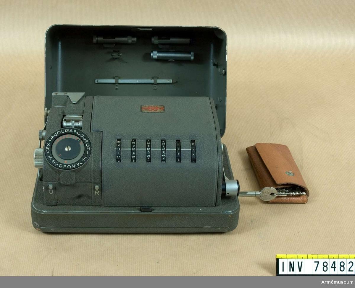 """Grupp I VI. Dechiffreringsapparat med fodral från början av 1950-talet jämte kataloger och specifikationer. Svenska försvaret använder benämningen Krypteringsapparat 204 (kryapp 204).  Tillverkaren Hagelin Kryptos benämner den C-52. Tillverkningsnr 10421.   Samhörande Fodral av väv m rem av läder, 4st nycklar i fodral, på lockets insida finns fästade: 1st """"oiler"""" 1st """"ink roller tube"""", 1st """"tube for spare lugs (17 st i), 1st """"lug tweezers"""", 1st """"skrew driver"""" saknas. I ett brunt kuver finns """"pinn setting tool"""" samt 2 st reservdelskataloger (benämningarna hämtade från dom) och 2 st specifikationer.   Svenska försvarets benämning hämtad från """"M-nummer katalogen 1971 okt"""". 90-06-26 EW. PS böckerna förvaras i militärtrycksbiblioteket."""