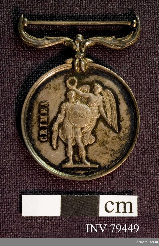 Grupp M.  Medaljen har en fastsittande, rikt utsirad bandhållare samt starkt upphöjd kontur. Åtsidan: VICTORIA REGINA 1854. Drottningens huvud åt venster med grekisk koaffyr och diadem. Frånsidan: Till venster på tvären: CRIMEA. I mitten en romersk krigare, hållande i högra handen en fackla? och med den vänstra framför sig en rund sköld, var synes ett på marken gående lejon inom en ornerad ram. Snett upptill till höger synes Fama i gestalt av en bevingad kvinna i begrepp att med en lagerkrans pryda krigarens huvud.