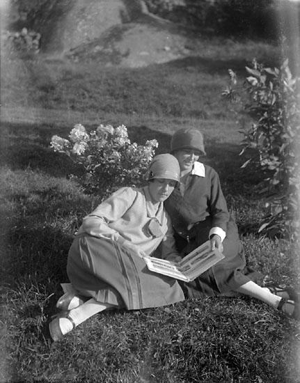 """Enligt senare noteringar: """"Tekla Börjesson-Eld och Elsa Teng i trädgården, med fotoalbum""""."""