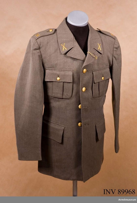 Stl 96 II .Av samma snitt som uniform m/1939. Daglig dräkt av gråbrungrönt  tyg. Bärs till mörkt gråbrungröna byxor. Tjänstetecken  mattförgyllda.