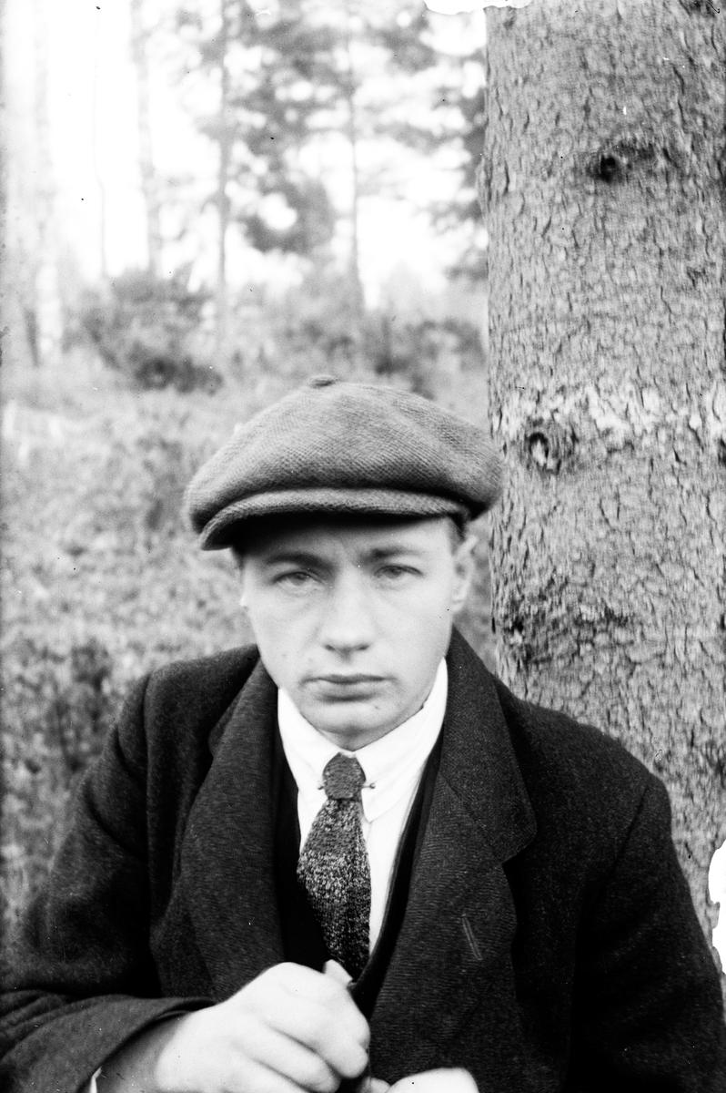 Gustav Andersson klädd i kostym och keps, med buskar och träd i bakgrunden.