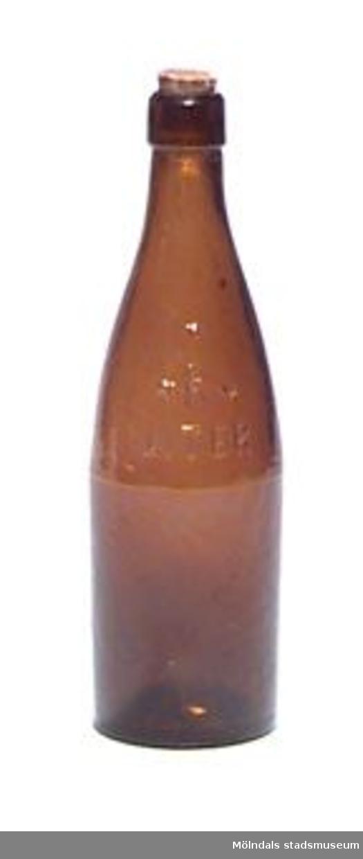 """Brun flaska med bevarad kork. Inpressat i glaset: """"* R * 1/3 LITER"""".Tillvaratagen av givaren i Landala (1968?)."""