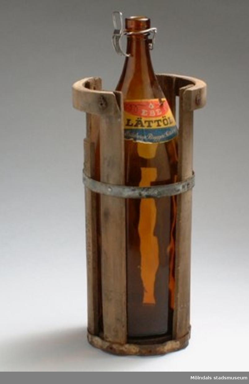 """En bräda i höljet saknas, en annan är utbytt och flera spikar saknas.Flaskan i brunt glas med pappersetikett: """" I EBE LÄTTÖL INNEHÅLLER SACKARIN Eriksbergs Bryggeri Göteborg, AKTIEBOLAGET PRIPP & LYCKHOLM GÖTEBORG"""".Porslinskorken saknas."""
