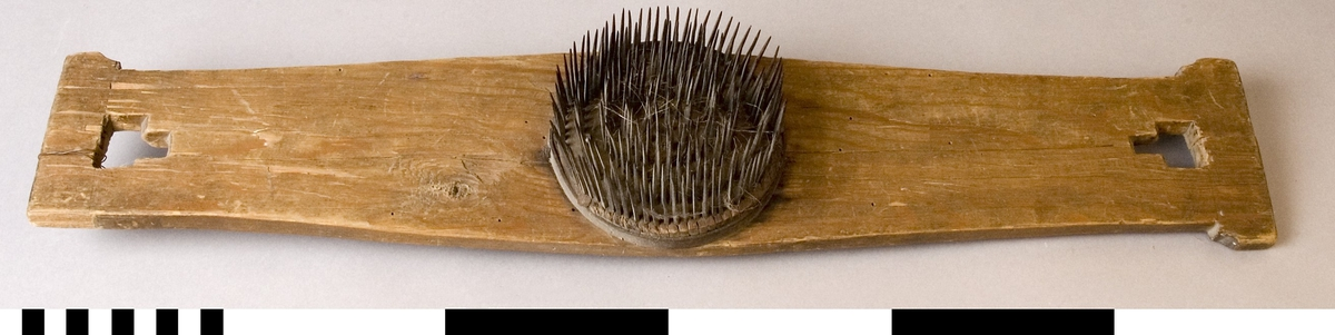 Häckla, handgjord av furuträ. Kluven, kontursågad. Fyrkantigt skurna hål i var ände. Konturerad ytterlinje. I mitten en rund yta med smala piggar av järn, tät som en finhäckla.