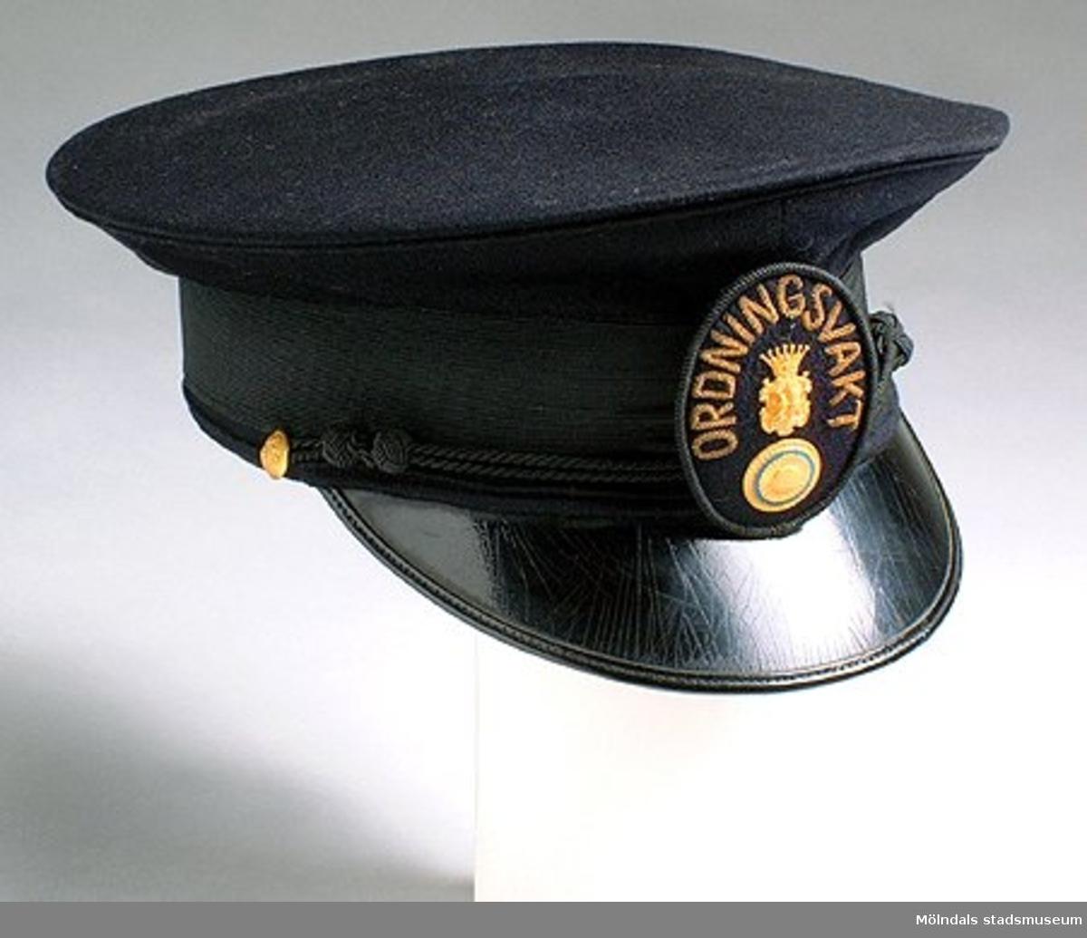 """Blå uniformshatt med skärm. Märke med """"Ordningsvakt"""" på. Sven Kjellberg var ordningsvakt vid dansbanan på Blåbärskullen i Mölnlycke. Arbetade i väveriet på Mölnlycke fabriker 1916-1969."""