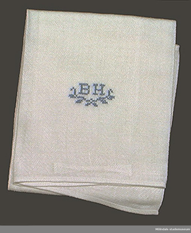 Vit handduk med Korsstygnsmonogram BH i blått.(=herrhandduk).