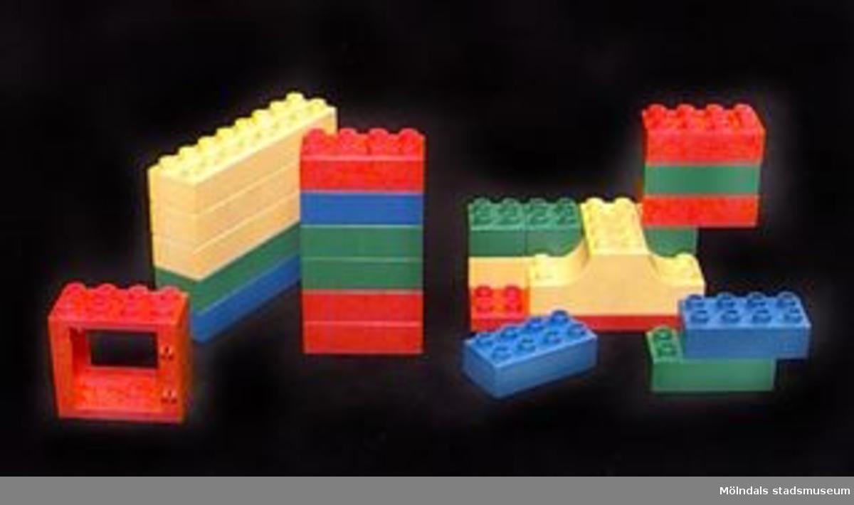 """Byggklossar i plast av Duploformatet, se MM02361.Samlingen omfattar 27 bitar i olika färg och format. Längden varierar mellan 30-130mm.H: 20 mm. Förutom klossarna finns ett rött fönster. L: 63 mm. B: 32 mm. H: 62 mm.Somliga är märkta """"Kullerbyttan"""". Gåva av Katrinebergs daghem."""