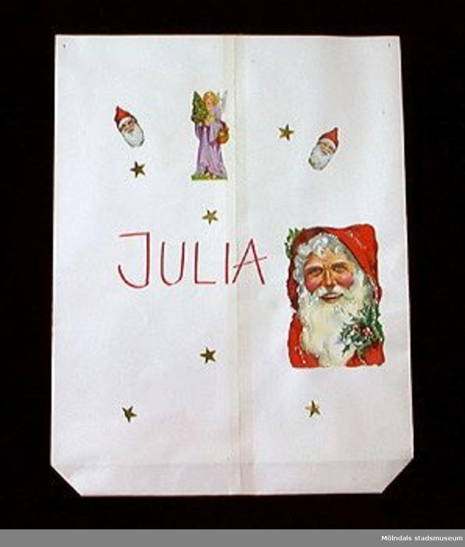 En påse i form av en tomte. Tillverkad av vanligt vitt papper, som har vikts och tejpats ihop till en modell av ordinär påstyp. På båda utsidor har tomtebokmärken, änglar och små guldstjärnor klistrats. Märkt: JULIA , textat med rött på påsens mitt. (Sannolikt en påse för utdelning i samband med julfirande vid daghemmet).Tidigare sakord: tomtepåse.Gåva från Katrinebergs daghem genom Birgitta Bilting.