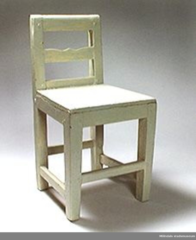 Ljusgrå barnstol med raka ben och plan träsits (240 mm lång och 320 mm. höjd från golv).Benen stadgas av fyra tvärslåar nedtill. Målad i flera lager. Ytterst en ljusgrå färg (av lacktyp). Öppen rygg med horisontell ryggbricka.