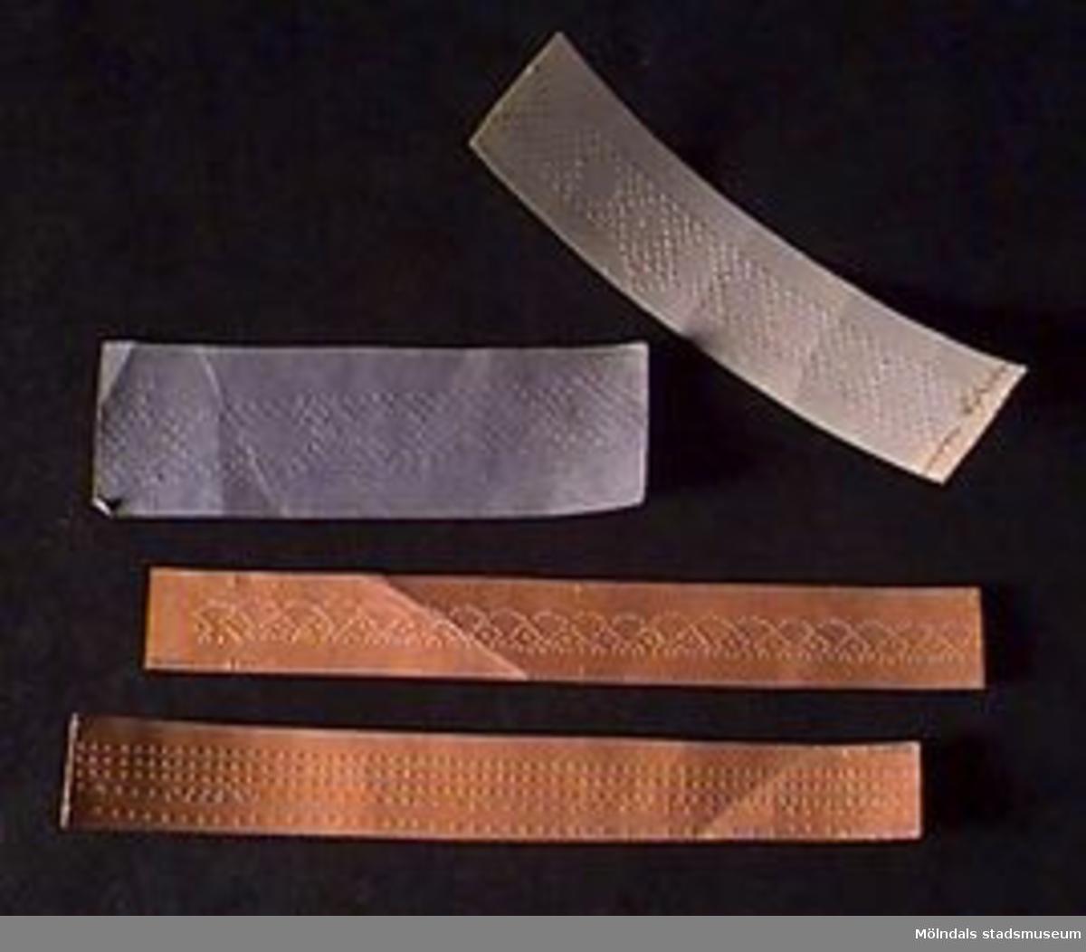 """Knyppelmönster på brun knyppelpapp respektive vanligt, kraftigt papper i grönt, blått och beige. Alla mönstren är perforerade efter knyppling.MM02824:1 (det bredaste mönstret) har måtten: L 322, B 68. Skrivet med blyerts: """"20 par"""".:2 (det längsta) har måtten: L 386, B 35. Ritat med blyerts, samt skrivet: """"9 par"""" och """"Gunvor Adelberth"""". :3 L 344, B 45. Skrivet med blyerts: """"Udd och stad"""", """"9 par"""", """"Gunvor Adelberth Klass ll"""". Även ett namn oläsligt.:4 L 338, B 46. Ritat med bläck. Skrivet med blyerts: """"Gunvor Adelberth"""", """"8 par"""" samt """"1 par ---garn-"""" (delvis oläsligt). Samma text på baksidan.:5 (L 230, B 94) och :6 (L 230, B 99). Klippta i vinkelform. Ritat med blyerts.:7 L 25, B 65. Skrivet med blyerts: """"delberth Klass lll B"""" (papperet avklippt mitt i namnet).:8  L 230, B 52. Ritat med blyerts. Skrivet med bläck: """"nvor Adelber"""" (papperet avklippt mitt i namnet).:9 L 330, B 35. Skrivet med blyerts: """"Gunvor Adelberth"""", dock nästan bortnött.:10 och :11 Ritat med blyerts. :12-17 Utan märkning.Gunvor Otter (f. 1916-12-21), ursprungligen från Gävle, flyttade till Toltorpsdalen (Fotbollsgatan 17) 1959. Till Bifrost flyttade hon 1991. Gunvor Otter är f.d. gymnasielärare i historia och svenska. 1955-1971 ca arbetade hon på Flickläroverket, därefter på Hvitfeldtska fram till pensioneringen 1981."""