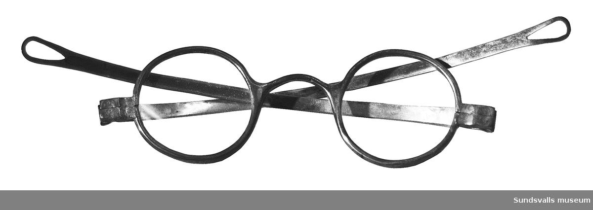 Ett par glasögon med båge i silver stämplade AGÅ, S, D7. De är tillverkade av Adam Gabriel Åberg (1857-1919), i Sundsvall 1906.