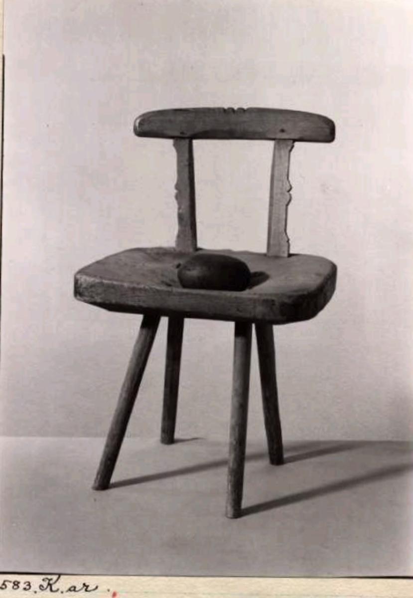 Saltstol av trä. Ryggbricka med profilerat krön. Ryggbrickan är fäst i sits med två raka ryggstolpar. Ryggstolparna är utåt från ryggen profilsågade med form som en pilbåge.Sitsen består av ett gediget hugget stycke trä med en nedsänkning i mitten. Runt om sitsen bildas en kraftig sarg. I sitsen finns fyra ben. Benen är formade som stavar med tappning in i sitsen. I mitten på sitsen finns en malsten .