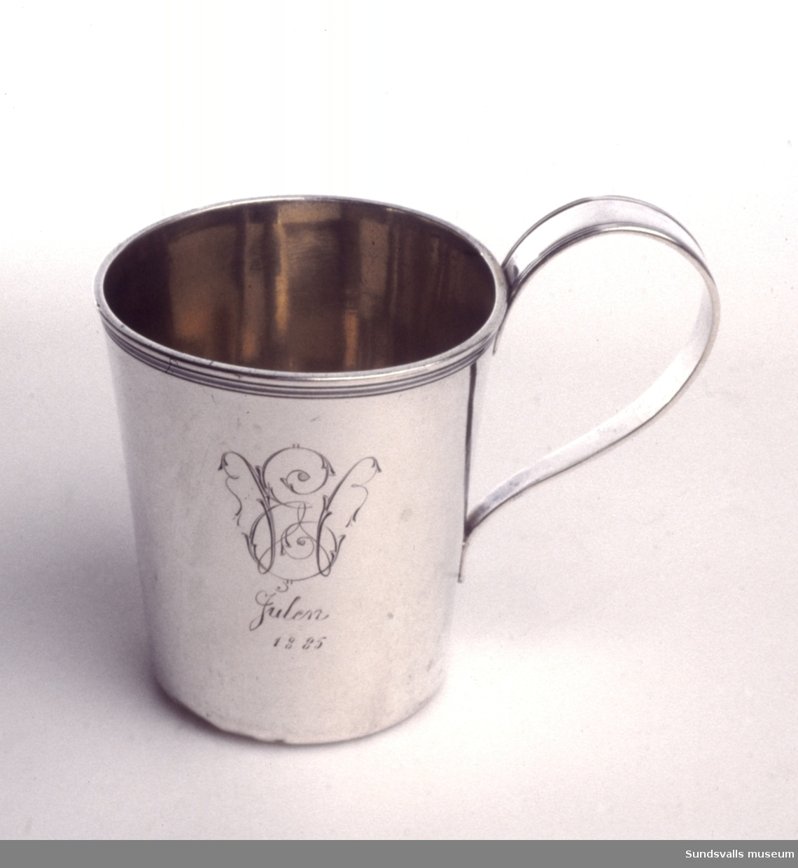 Ölsejdel med invändig förgyllning. Svag konisk form, slät yta och profilerad kant. Böjd profilerad hänkel. Stplr: Gustaf Möllenborg, Stockholm 1829.