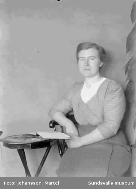 Kvinna sitter vid ett litet bord med en bok uppslagen.