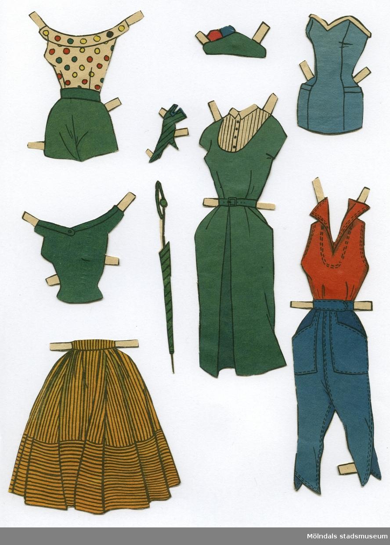 """Pappersdocka med kläder och tillbehör, urklippt ur tidning på 1950-talet. Docka och kläder är märkta """"Ann-Caroline"""" på baksidan - dockans namn. Dockan föreställer en ung kvinna, iklädd axelbandslösa underkläder av baddräktsmodell och skor. Garderoben består av två klänningar, jacka, set med blus och shorts, set med blus och långbyxor, två toppar, kjol, två sol- och baddräkter, hatt och handske. Hon har också tillbehör som paraply och solglasögon. I materialet finns två texturklipp. På den ena står det: """"Påklädningsdockan Ann-Caroline"""". Den andra är en beskrivning av dockan och hur man kan leka med henne. Docka och kläder förvaras i ett brunt kuvert, märkt med blyerts """"Ann-Caroline"""", men är ursprungligen från Göteborgs Järnvägsmäns Platsorganisation."""