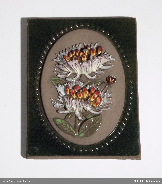 """Grön keramiktavla med Vildkaprifol som motiv. Bak på tavlan finns texten """"DISIGN jimo   881   jie   Vildkaprifol Bohuslän (mycket slitet)"""" inristat. Tavlan är från början av 1970-talet. Formgivare var Annika Kihlman som arbetade på företaget Jie-Keramik mellan 1971-1975."""
