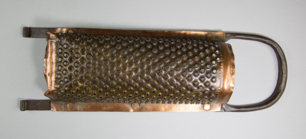 Rivjärn av koppar och järn. Kopparplåten är nitad vid en böjd stång av järn. Plåten är perforerad med en spik. Kopparplåten är delvis förtent.