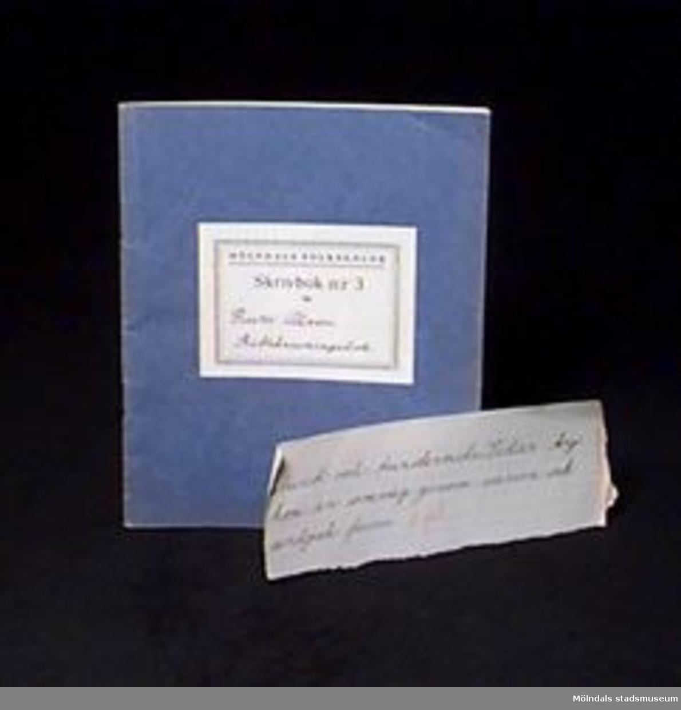 """:1 Blå skrivbok med linjerade sidor. På omslaget en etikett med tryckt text: """"MÖLNDALS FOLKSKOLOR/Skrivbok n:r 3 för"""" samt skrivet med bläck: """"Rune Olsson Rättskrivningsbok"""". Mått: L 206 mm, B 171 mm, H 2 mm.:2 En bit av ett linjerat blad, tre kanter rivna. Text skriven med bläck och rödpenna. Mått: L 182 mm, B 67 mm.Givaren gick hela sin skoltid i Toltorpsskolan."""